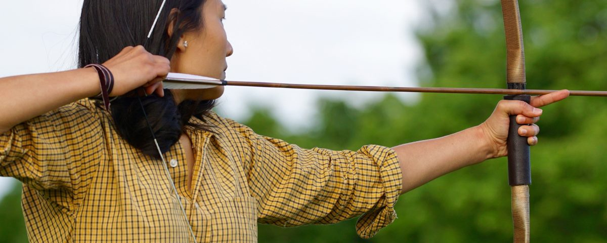 Female archer drawing back bow